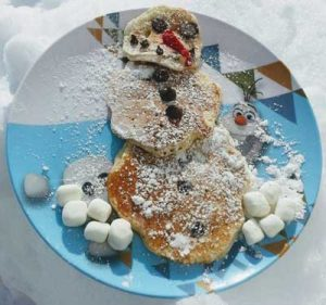 Snowman Pancakes Recipe - 3 pancakes on a plate with confectioner's sugar and marshmallows