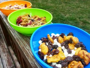 Homemade Trail Mix Recipes for Kids Featuring Tiny Snacks like Yogurt Raisins, Goldfish, Raisins, Craisins, mini Marshmallows, and more in colorful bowls on a wooden railing