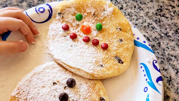 Snowman Pancakes Featuring M&Ms, Candy Corn, and Chocolate Chips. with Child's Hand
